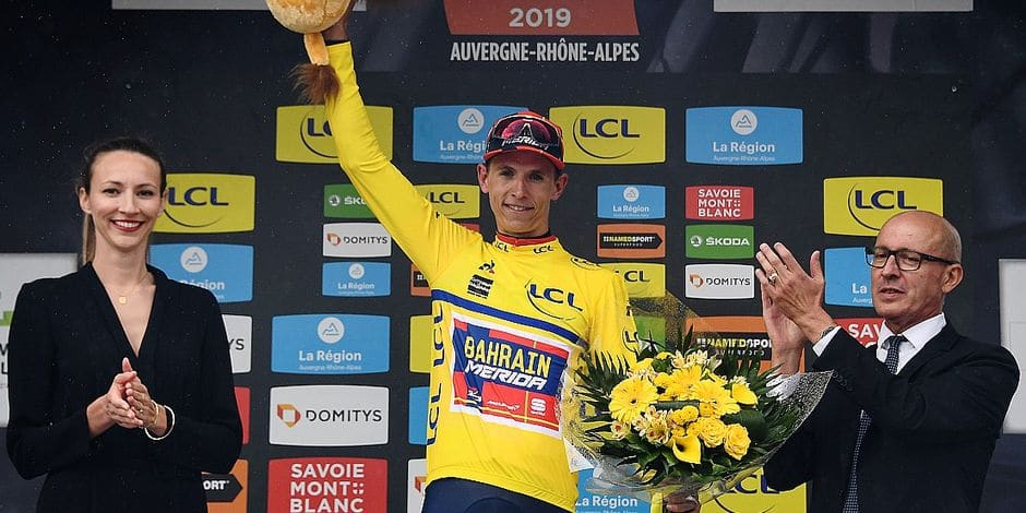 Bahrain-Merida rider Belgium's Dylan Teuns celebrates his overall leader's yellow jersey on the podium at the end of the third stage of the 71st edition of the Criterium du Dauphine cycling race, 177 km between Le Puy-en-Velay and Riom, in Riom, on June 11, 2019. (Photo by Anne-Christine POUJOULAT / AFP)