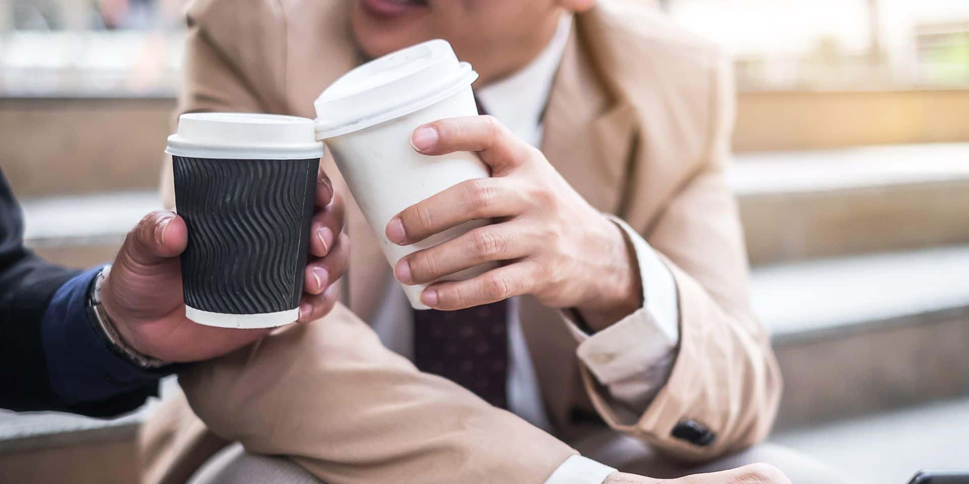 Close-up,Of,Two,Business,Partners,Holding,Cups,Of,Coffee