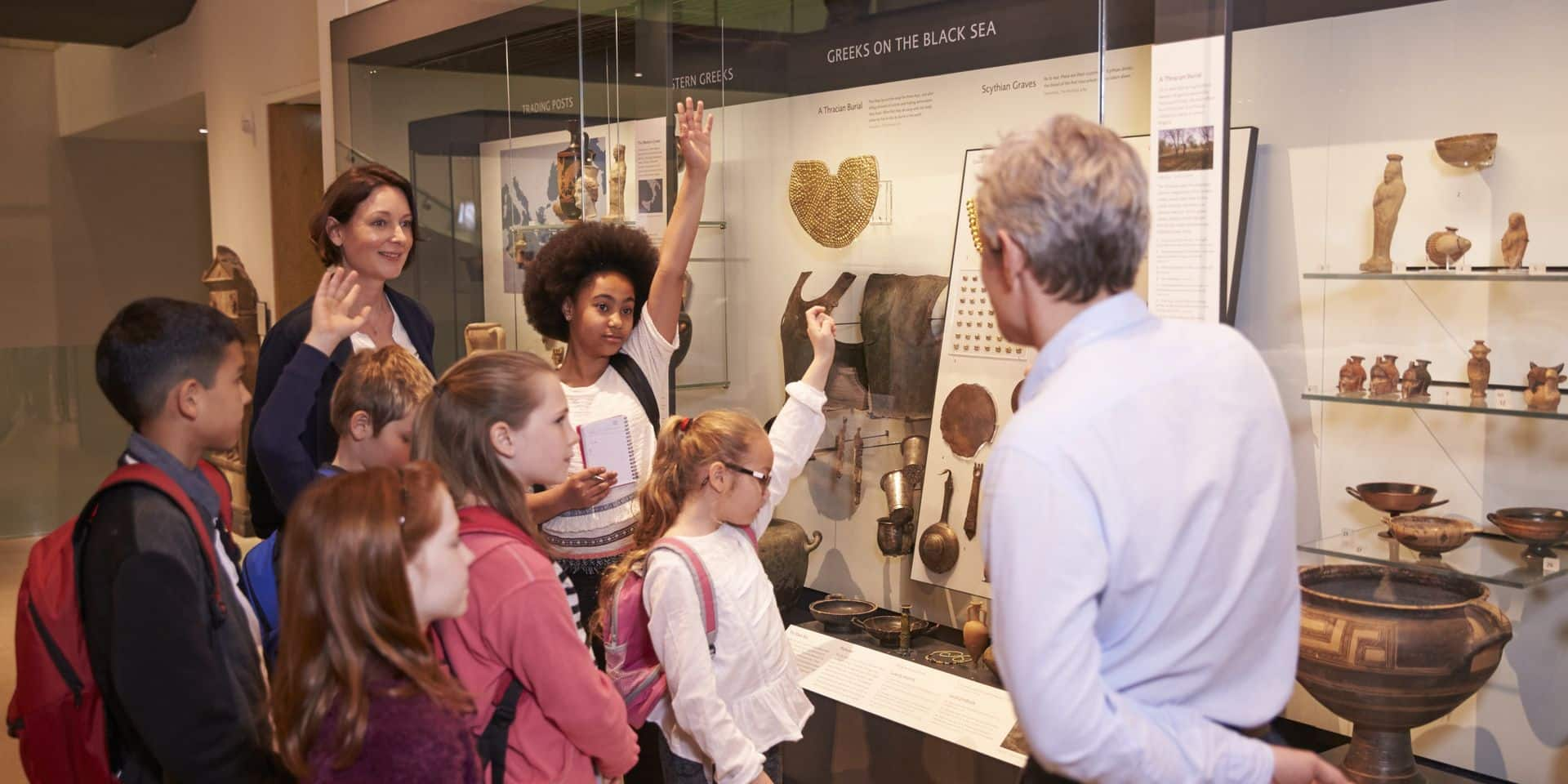 Students,Looking,At,Artifacts,In,Case,On,Trip,To,Museum