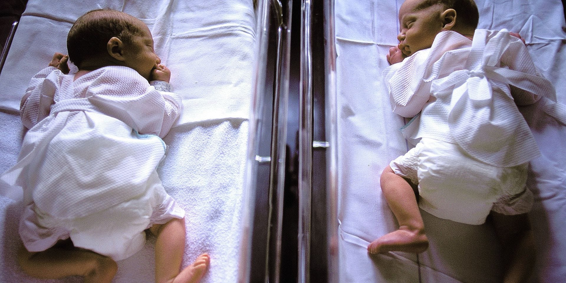 2 nouveaux-nés jumeaux (6 heures) dormant à plat ventre dans 2 petits lits