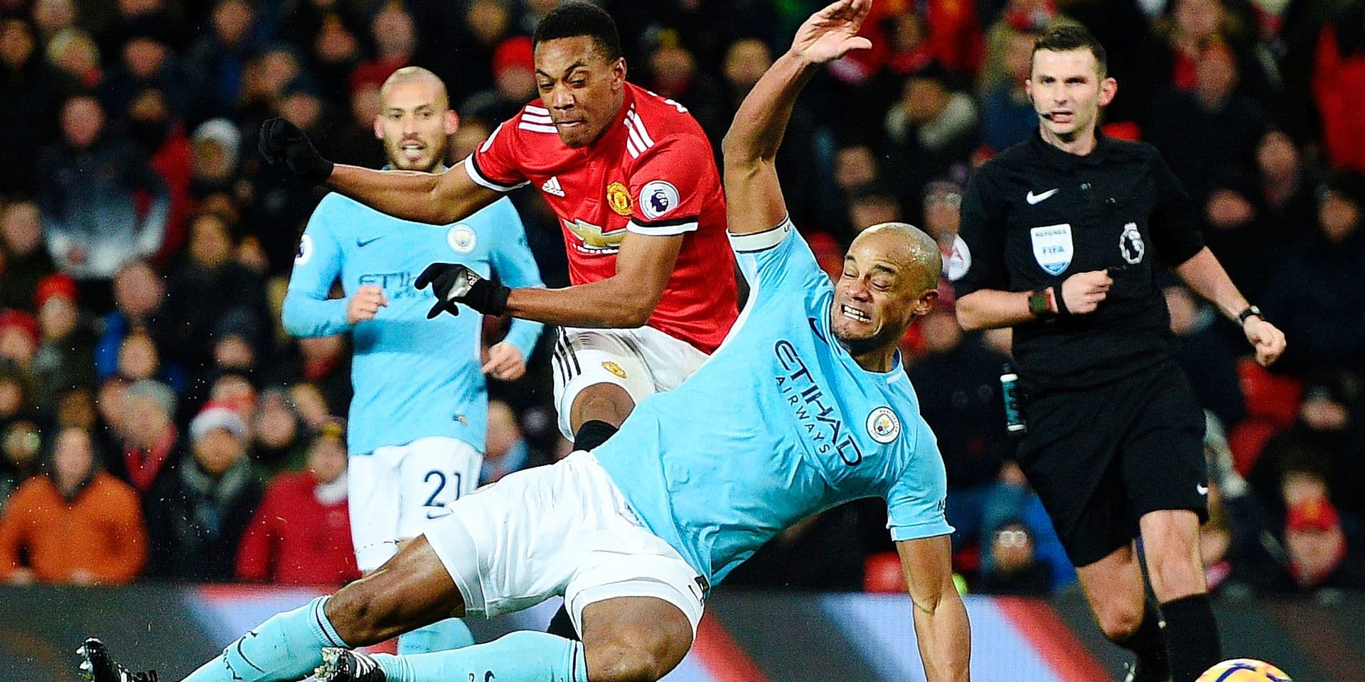 Manchester City's Belgian defender Vincent Kompany (R) dives across to block a shot from Manchester United's French striker Anthony Martial (L) during the English Premier League football match between Manchester United and Manchester City at Old Trafford in Manchester, north west England, on December 10, 2017. / AFP PHOTO / Oli SCARFF / RESTRICTED TO EDITORIAL USE. No use with unauthorized audio, video, data, fixture lists, club/league logos or 'live' services. Online in-match use limited to 75 images, no video emulation. No use in betting, games or single club/league/player publications. /