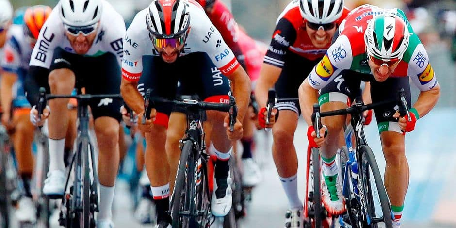 Team UAE Emirates rider Colombia's Fernando Gaviria (C) compete the final sprint flanked by Team Deceuninck rider Italy's Elia Viviani (R) during the stage three of the 102nd Giro d'Italia - Tour of Italy - cycle race, 220kms from Vinci to Orbetello on May 13, 2019. - Team UAE Emirates rider Colombia's Fernando Gaviria won the stage after Team Deceuninck rider Italy's Elia Viviani has been disqualifited by the race jury. (Photo by Luk BENIES / AFP)