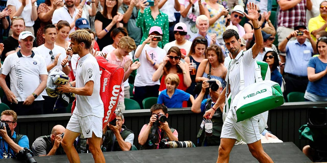 Serbia's Novak Djokovic (R) waves as he leaves the court with Belgium's David Goffin (L) after winning their men's singles quarter-final match on day nine of the 2019 Wimbledon Championships at The All England Lawn Tennis Club in Wimbledon, southwest London, on July 10, 2019. (Photo by Daniel LEAL-OLIVAS / AFP) / RESTRICTED TO EDITORIAL USE
