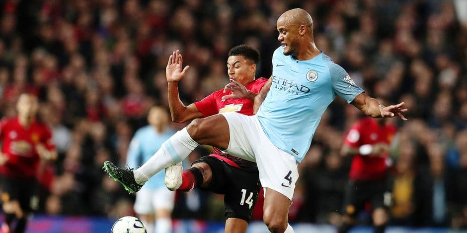 Manchester United's Jesse Lingard fights for the ball with Manchester City's Vincent Kompany, right, during the English Premier League soccer match between Manchester United and Manchester City at Old Trafford Stadium in Manchester, England, Wednesday April 24, 2019. (AP Photo/Jon Super)