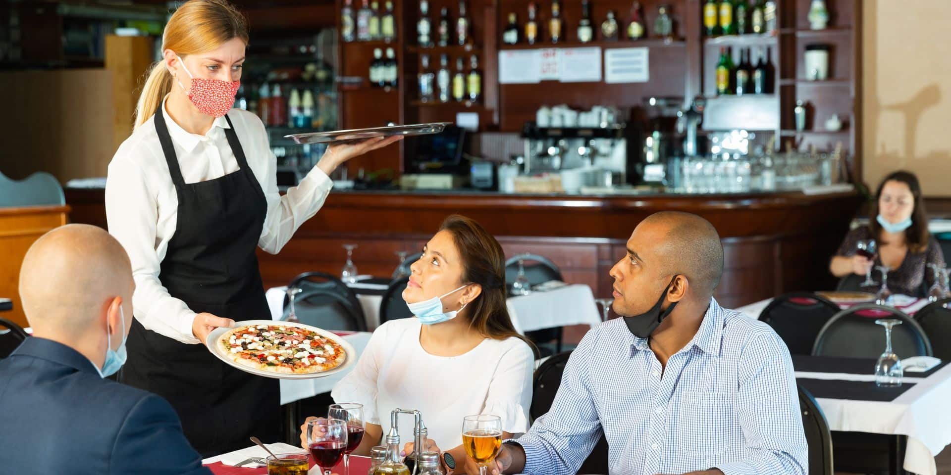 Polite,Waitress,In,Protective,Mask,Bringing,Ordered,Pizza,To,Friends