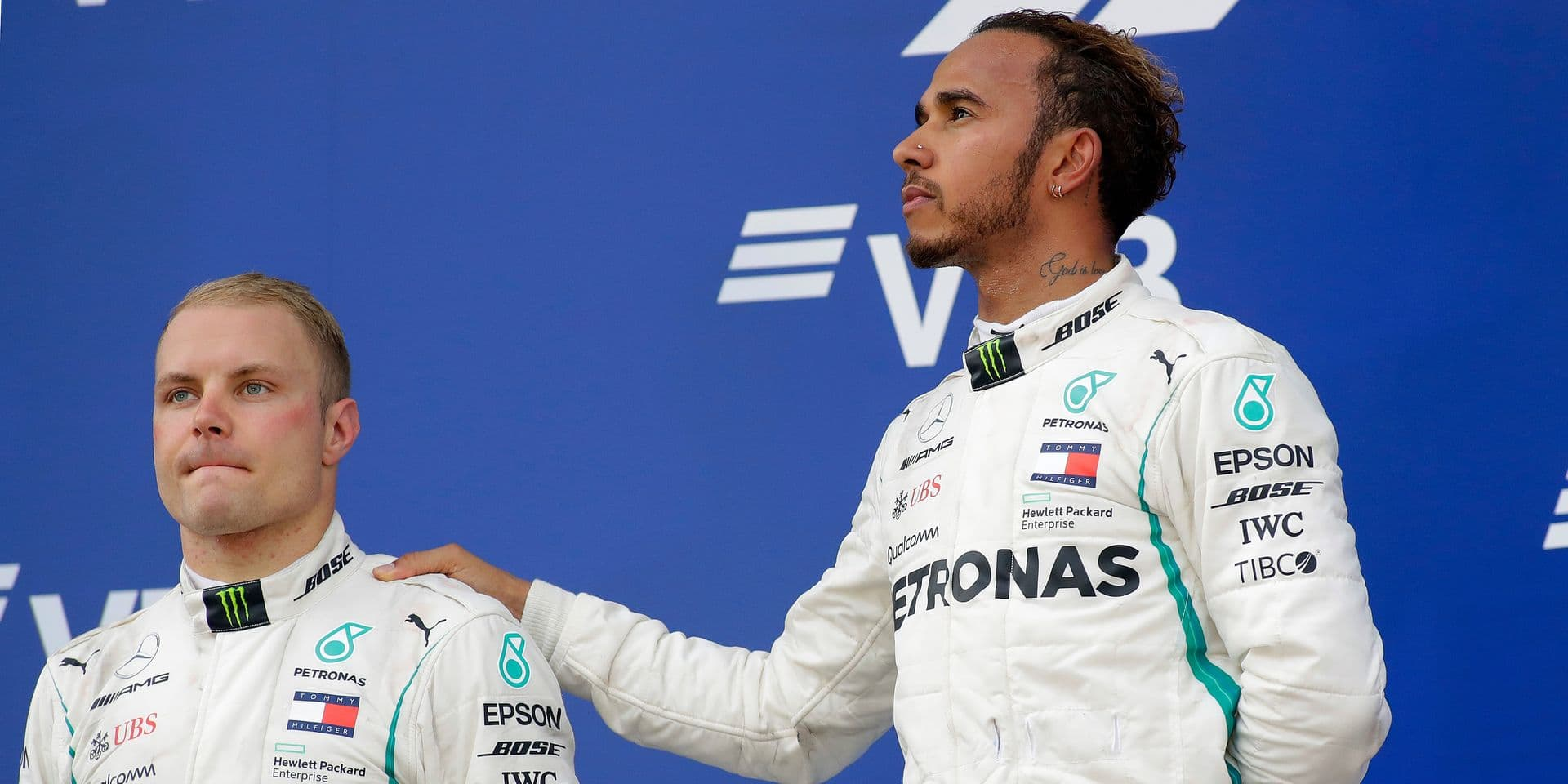 Second placed Mercedes driver Valtteri Bottas of Finland, left, and winner Mercedes driver Lewis Hamilton of Britain listen to the anthems after the Russian Formula One Grand Prix at the Sochi Autodrom circuit in Sochi, Russia, Sunday, Sept. 30, 2018.(AP Photo/Sergei Grits)