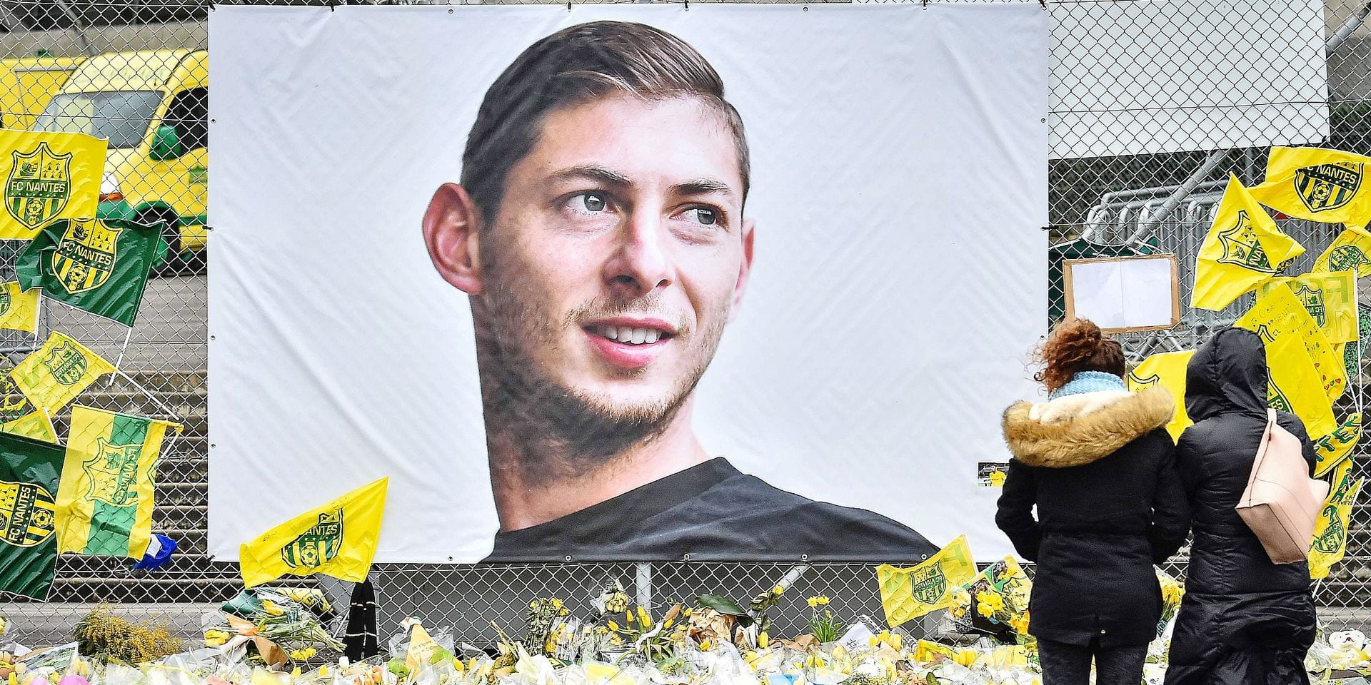 People look at yellow flowers displayed in front of the portrait of Argentinian forward Emiliano Sala at the Beaujoire stadium in Nantes, on February 8, 2019. - FC Nantes football club announced on February 8, 2019 that it will freeze the #9 jersey as a tribute to Cardiff City and former Nantes footballer Emiliano Sala who died in a plane crash in the English Channel on January 21, 2019. (Photo by LOIC VENANCE / AFP)