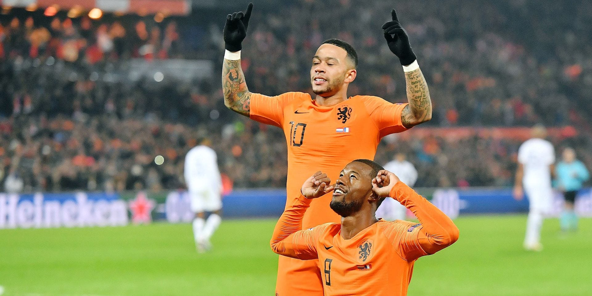Netherlands' midfielder Georginio Wijnaldum (bottom) celebrates with Netherlands' forward Memphis Depay after scoring a goal during the UEFA Nations League football match between the Netherlands and France at the Feijenoord stadium in Rotterdam on November 16, 2018. (Photo by EMMANUEL DUNAND / AFP)
