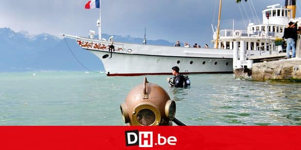 """Thierry Goel dives with a Russian diver helmet from 1950 while a steamboat, CGN, sails during a demonstration on the sideline the 9th edition of """"Net'Leman"""", a day where volunteers clean-up the Lake of Geneva and its shores, in Vevey, Switzerland, Saturday, May 26, 2018. (Laurent Gillieron/KEYSTONE via AP)"""
